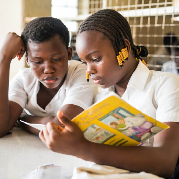 Sarah James (left), 13 years old, and Bintu Rabie Conteh (right), 12, are enrolled in Rising Academy Network's Tengbeh Town school as JSS1 students. Bintu is helping Sarah, a