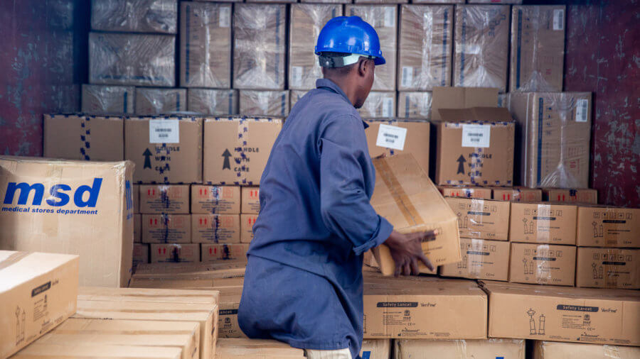 A man at Tanzania's Medical Stores Department loads a shipment onto a truck to be delivered.